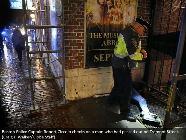 Boston Police Captain Robert Ciccolo keeps an eye on a man who had gone out on Tremont Street. (Craig F. Walker/Globe Staff)