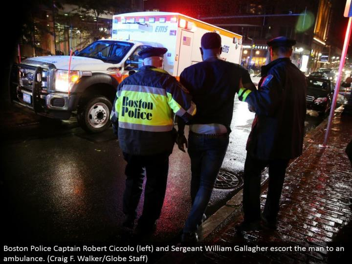 Boston Police Captain Robert Ciccolo (left) and Sergeant William Gallagher escort the man to an emergency vehicle. (Craig F. Walker/Globe Staff)