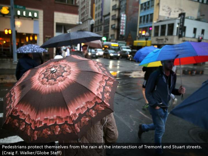 Pedestrians shield themselves from the rain at the crossing point of Tremont and Stuart avenues. (Craig F. Walker/Globe Staff)