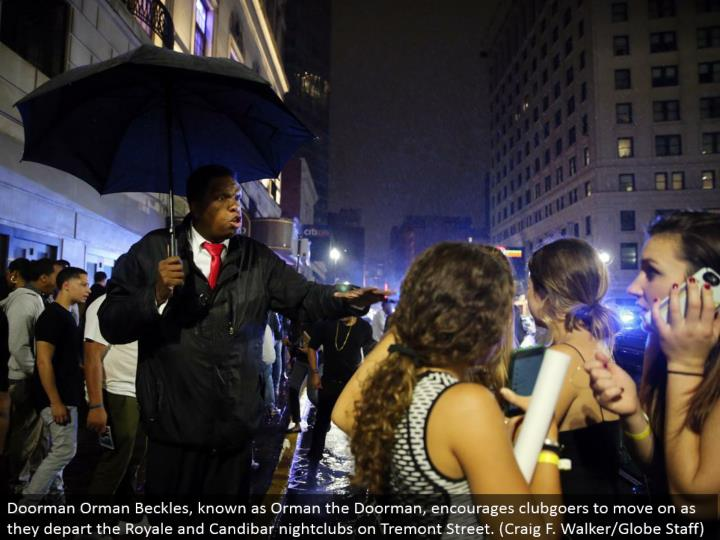 Doorman Orman Beckles, known as Orman the Doorman, urges clubgoers to proceed onward as they withdraw the Royale and Candibar dance club on Tremont Street. (Craig F. Walker/Globe Staff)