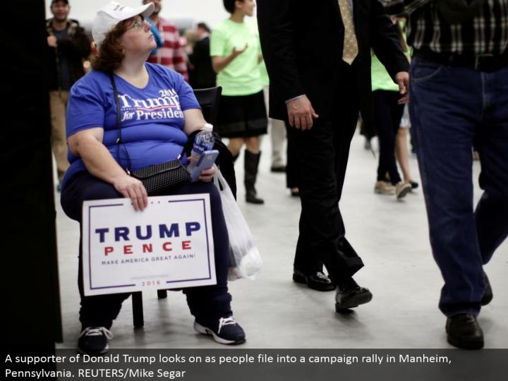 A supporter of Donald Trump looks on as individuals record into a battle rally in Manheim, Pennsylvania. REUTERS/Mike Segar
