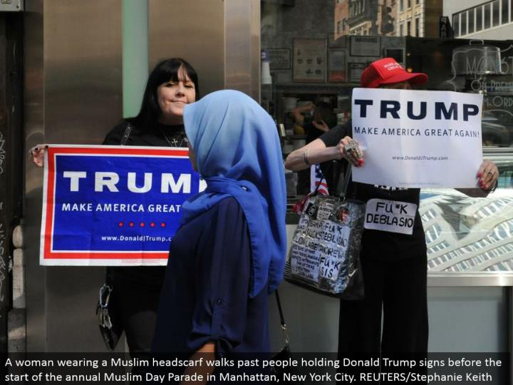 A lady wearing a Muslim headscarf strolls past individuals holding Donald Trump signs before the begin of the yearly Muslim Day Parade in Manhattan, New York City. REUTERS/Stephanie Keith