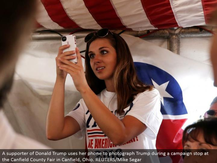 A supporter of Donald Trump utilizes her telephone to photo Trump amid a battle stop at the Canfield County Fair in Canfield, Ohio. REUTERS/Mike Segar