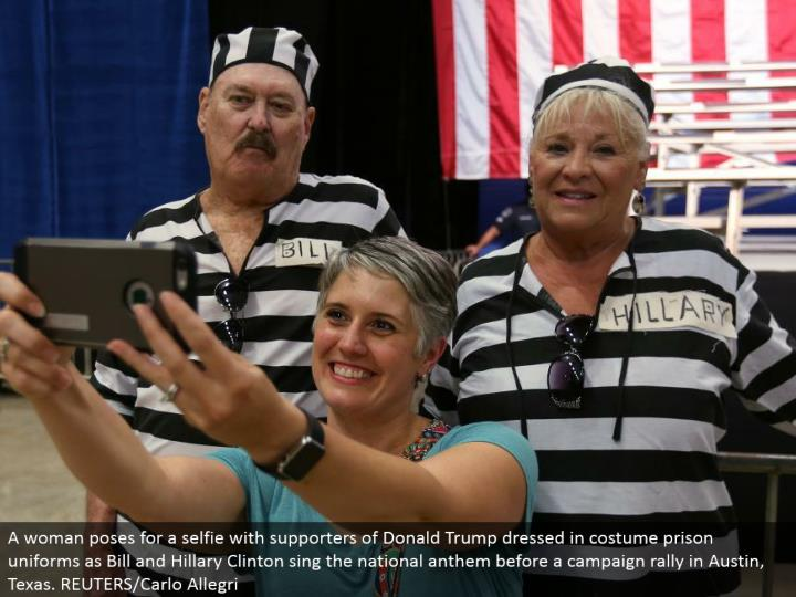 A lady postures for a selfie with supporters of Donald Trump wearing outfit jail regalia as Bill and Hillary Clinton sing the national song of devotion before a crusade rally in Austin, Texas. REUTERS/Carlo Allegri