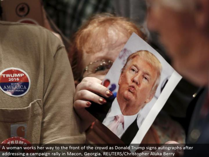 A lady works her way to the front of the group as Donald Trump signs signatures in the wake of tending to a battle rally in Macon, Georgia. REUTERS/Christopher Aluka Berry