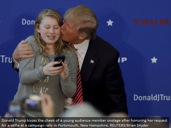 Donald Trump kisses the cheek of a youthful gathering of people part in front of an audience in the wake of respecting her demand for a selfie at a battle rally in Portsmouth, New Hampshire. REUTERS/Brian Snyder