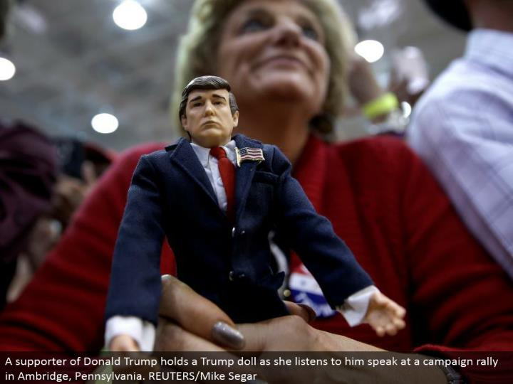 A supporter of Donald Trump holds a Trump doll as she listens to him talk at a crusade rally in Ambridge, Pennsylvania. REUTERS/Mike Segar