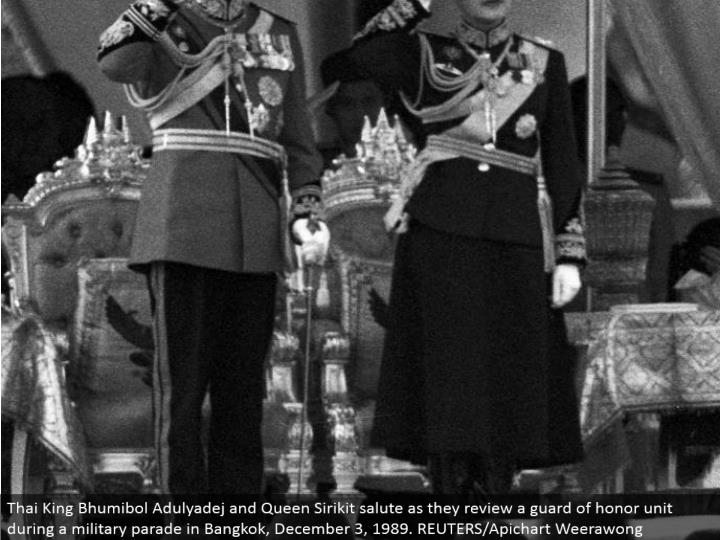 Thai King Bhumibol Adulyadej and Queen Sirikit salute as they audit a protect of respect unit amid a military parade in Bangkok, December 3, 1989. REUTERS/Apichart Weerawong