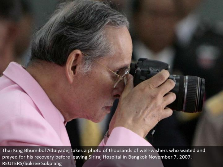 Thai King Bhumibol Adulyadej takes a photograph of a large number of well-wishers who sat tight and appealed to God for his recuperation before leaving Siriraj Hospital in Bangkok November 7, 2007. REUTERS/Sukree Sukplang