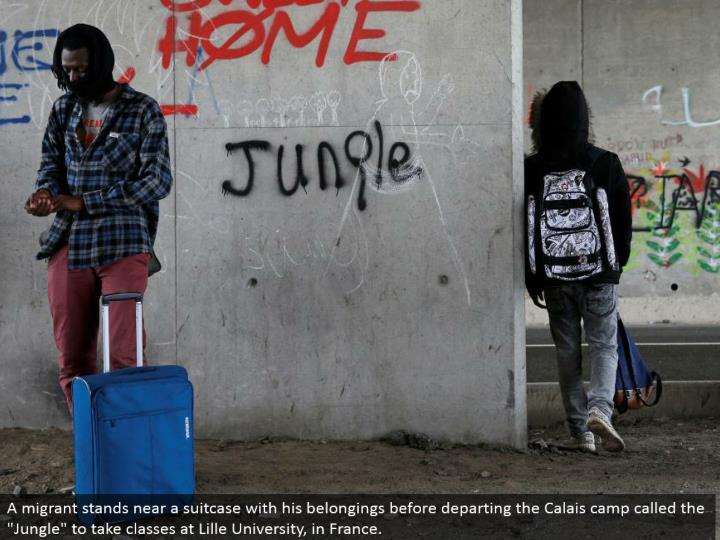 "A vagrant stands close to a bag with his possessions before withdrawing the Calais camp called the ""Wilderness"" to take classes at Lille University, in France."