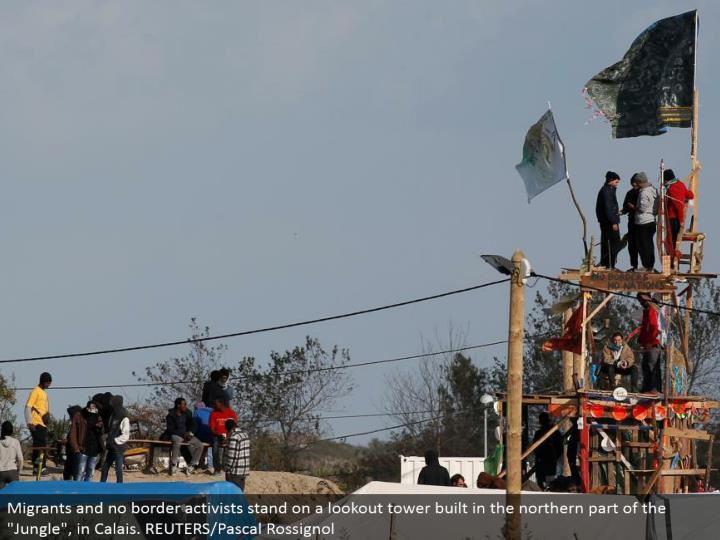 "Migrants and no fringe activists remain on a post tower worked in the northern part of the ""Wilderness"", in Calais. REUTERS/Pascal Rossignol"