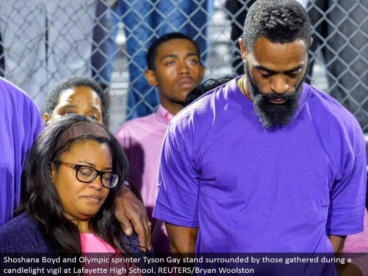 Shoshana Boyd and Olympic sprinter Tyson Gay stand encompassed by those assembled amid a candlelight vigil at Lafayette High School. REUTERS/Bryan Woolston