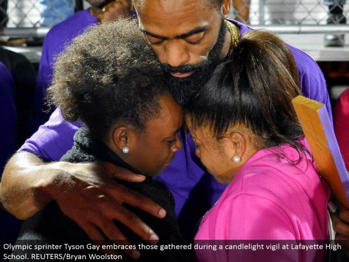 Olympic sprinter Tyson Gay grasps those accumulated amid a candlelight vigil at Lafayette High School. REUTERS/Bryan Woolston