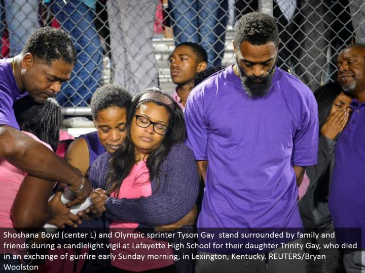 Shoshana Boyd (focus L) and Olympic sprinter Tyson Gay stand encompassed by family and companions amid a candlelight vigil at Lafayette High School for their little girl Trinity Gay, who passed on in a trade of gunfire early Sunday morning, in Lexington, Kentucky. REUTERS/Bryan Woolston