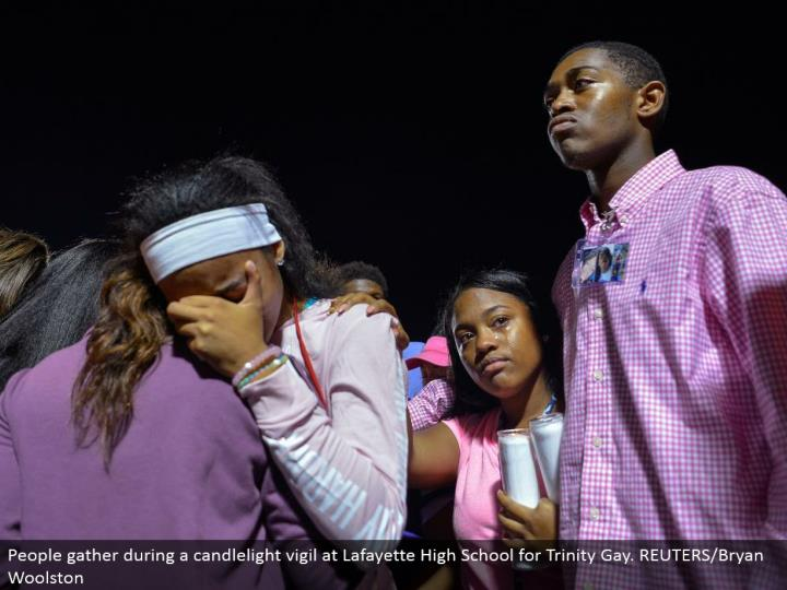 People accumulate amid a candlelight vigil at Lafayette High School for Trinity Gay. REUTERS/Bryan Woolston