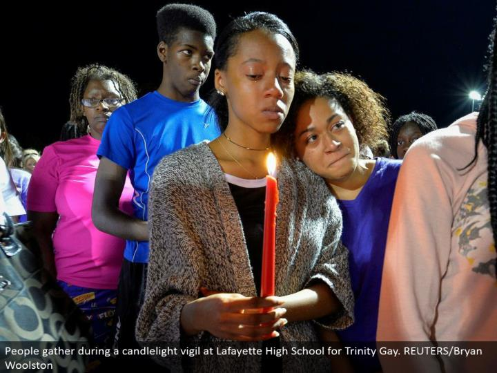 People assemble amid a candlelight vigil at Lafayette High School for Trinity Gay. REUTERS/Bryan Woolston