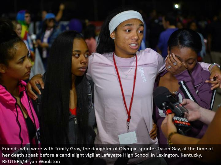 Friends who were with Trinity Gray, the girl of Olympic sprinter Tyson Gay, at the season of her demise talk before a candlelight vigil at Lafayette High School in Lexington, Kentucky. REUTERS/Bryan Woolston