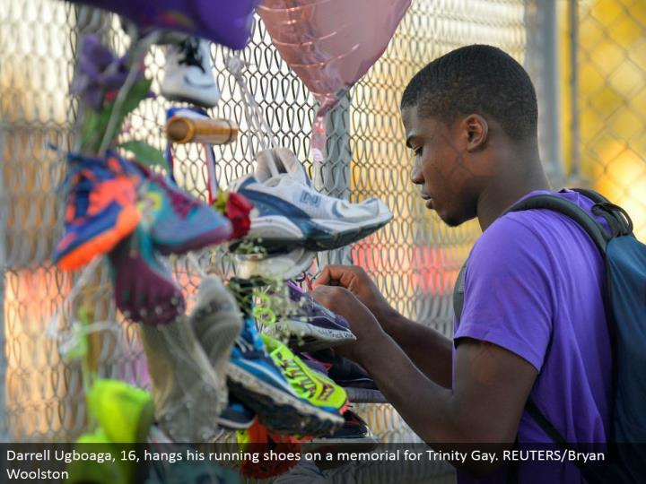 Darrell Ugboaga, 16, hangs his running shoes on a dedication for Trinity Gay. REUTERS/Bryan Woolston