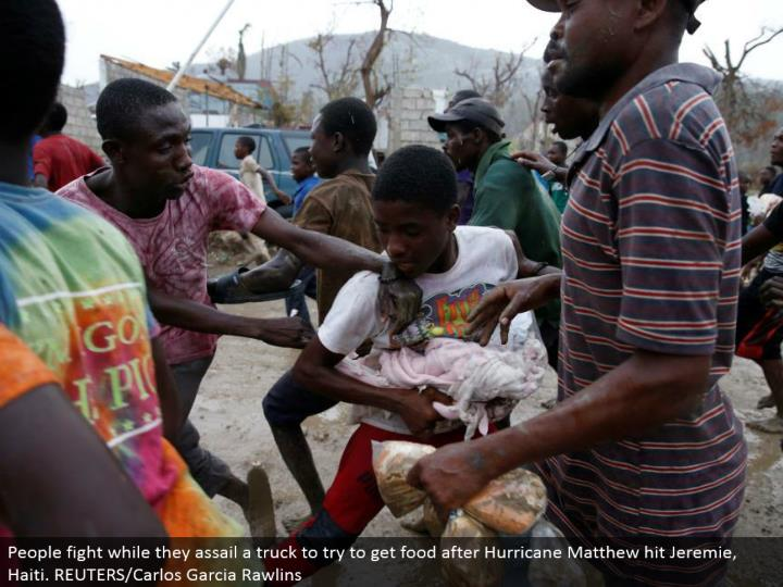 People battle while they assault a truck to attempt to get sustenance after Hurricane Matthew hit Jeremie, Haiti. REUTERS/Carlos Garcia Rawlins
