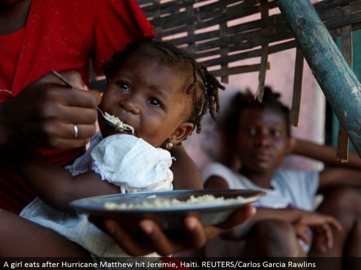 A young lady eats after Hurricane Matthew hit Jeremie, Haiti. REUTERS/Carlos Garcia Rawlins