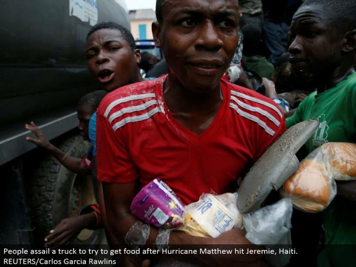 People assault a truck to attempt to get sustenance after Hurricane Matthew hit Jeremie, Haiti. REUTERS/Carlos Garcia Rawlins