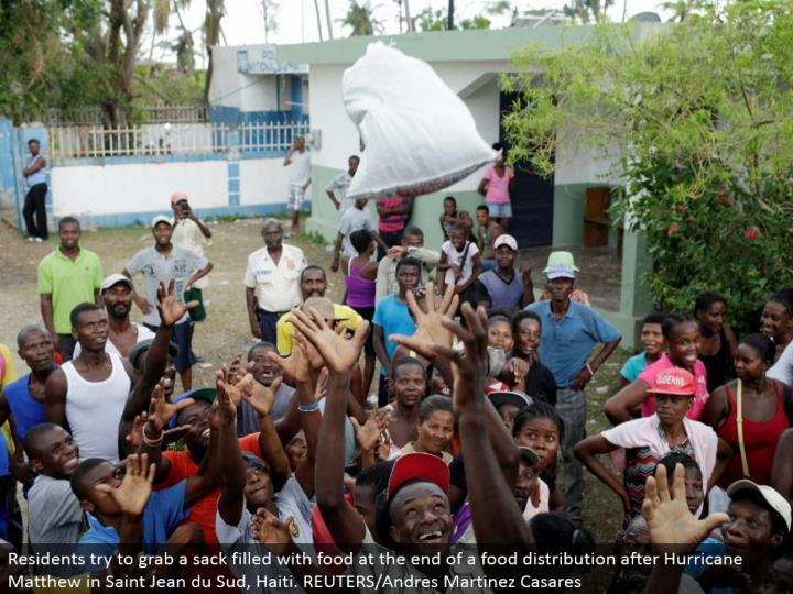 Residents attempt to get a sack loaded with sustenance toward the end of a nourishment circulation after Hurricane Matthew in Saint Jean du Sud, Haiti. REUTERS/Andres Martinez Casares