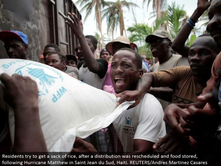 Residents attempt to get a sack of rice, after a dispersion was rescheduled and nourishment put away, after Hurricane Matthew in Saint Jean du Sud, Haiti. REUTERS/Andres Martinez Casares