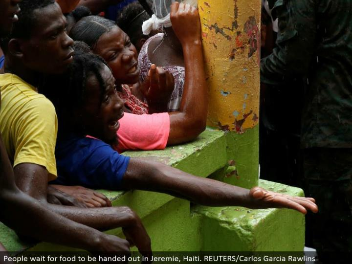 People sit tight for nourishment to be given out in Jeremie, Haiti. REUTERS/Carlos Garcia Rawlins