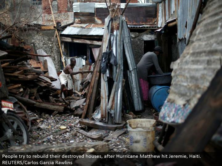 People attempt to revamp their demolished houses, after Hurricane Matthew hit Jeremie, Haiti. REUTERS/Carlos Garcia Rawlins