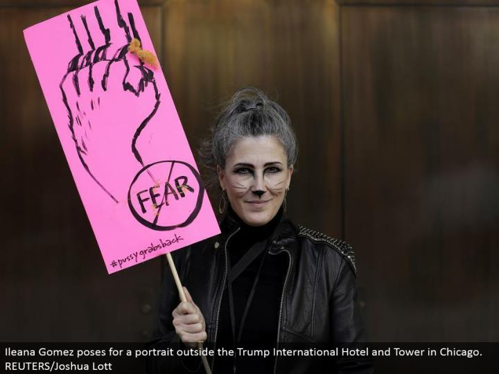 Ileana Gomez postures for a representation outside the Trump International Hotel and Tower in Chicago. REUTERS/Joshua Lott