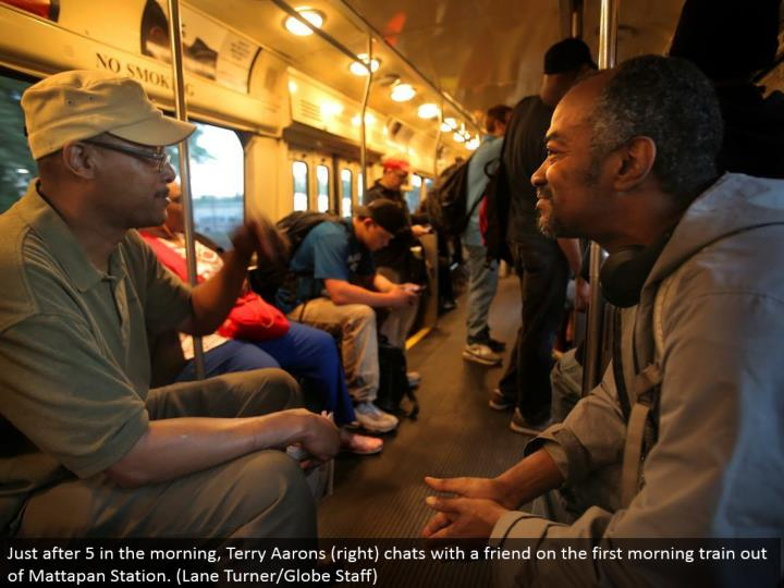 Just after 5 in the morning, Terry Aarons (right) visits with a companion on the principal morning train out of Mattapan Station. (Path Turner/Globe Staff)