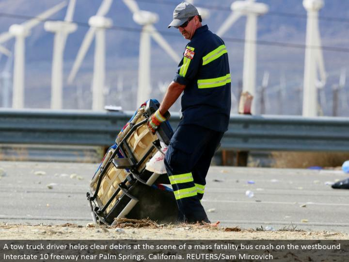 A tow truck driver clears trash at the scene of a mass casualty transport crash on the westward Interstate 10 turnpike close Palm Springs, California. REUTERS/Sam Mircovich