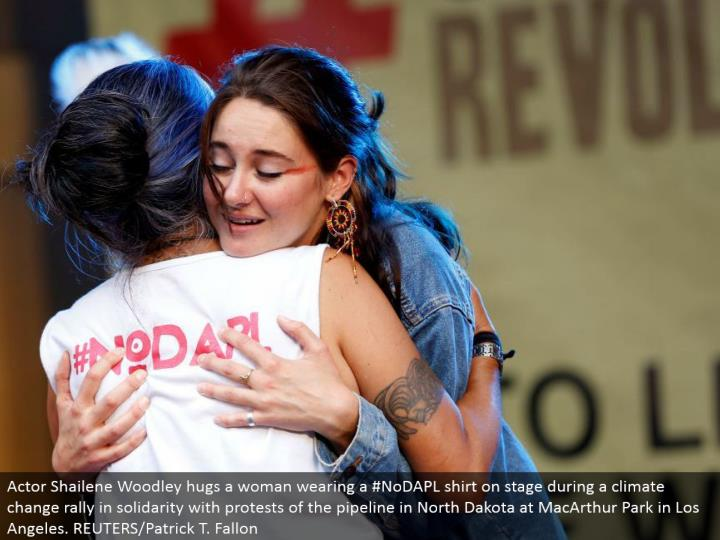 Actor Shailene Woodley embraces a lady wearing a #NoDAPL shirt in front of an audience amid an environmental change rally in solidarity with dissents of the pipeline in North Dakota at MacArthur Park in Los Angeles. REUTERS/Patrick T. Fallon