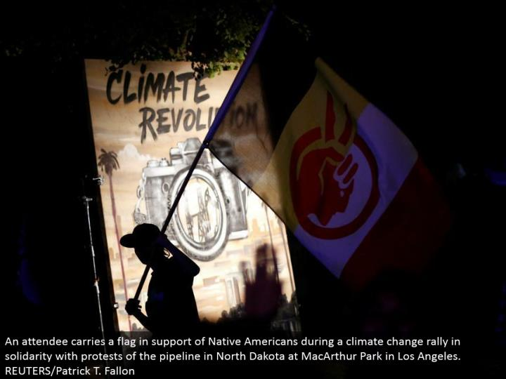 An participant conveys a banner in support of Native Americans amid an environmental change rally in solidarity with dissents of the pipeline in North Dakota at MacArthur Park in Los Angeles. REUTERS/Patrick T. Fallon