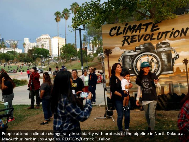 People go to an environmental change rally in solidarity with dissents of the pipeline in North Dakota at MacArthur Park in Los Angeles. REUTERS/Patrick T. Fallon