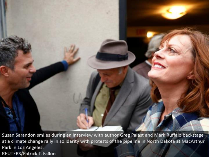 Susan Sarandon grins amid a meeting with creator Greg Palast and Mark Ruffalo backstage at an environmental change rally in solidarity with dissents of the pipeline in North Dakota at MacArthur Park in Los Angeles. REUTERS/Patrick T. Fallon