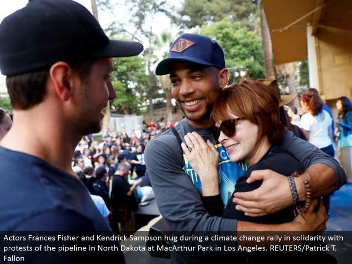 Actors Frances Fisher and Kendrick Sampson embrace amid an environmental change rally in solidarity with dissents of the pipeline in North Dakota at MacArthur Park in Los Angeles. REUTERS/Patrick T. Fallon