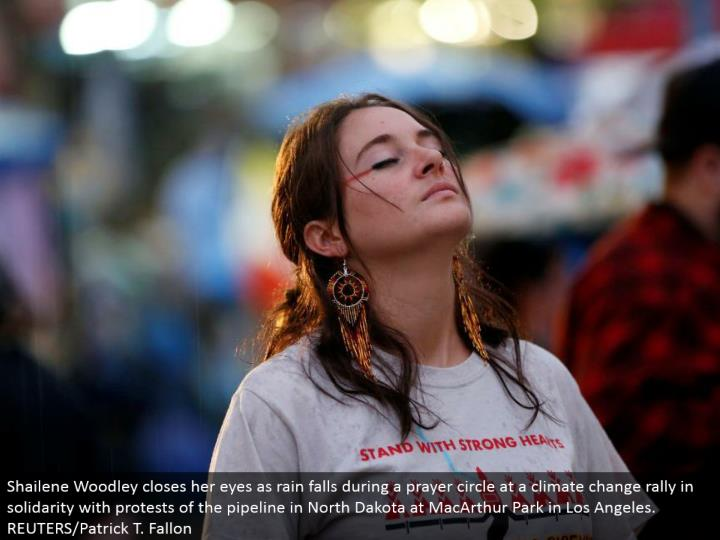 Shailene Woodley shuts her eyes as rain falls amid a supplication hover at an environmental change rally in solidarity with dissents of the pipeline in North Dakota at MacArthur Park in Los Angeles. REUTERS/Patrick T. Fallon