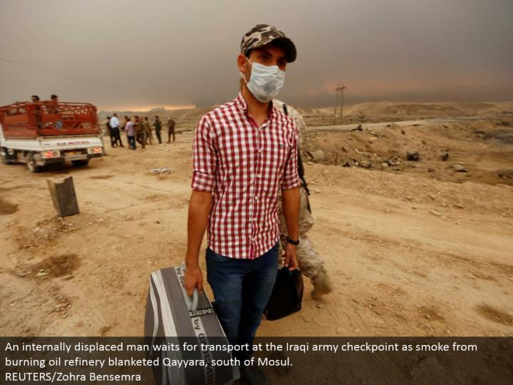 An inside uprooted man sits tight for transport at the Iraqi armed force checkpoint as smoke from smoldering oil refinery covered Qayyara, south of Mosul. REUTERS/Zohra Bensemra