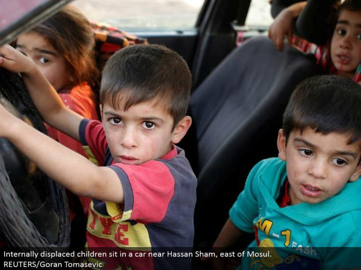 Internally dislodged youngsters sit in an auto close Hassan Sham, east of Mosul. REUTERS/Goran Tomasevic