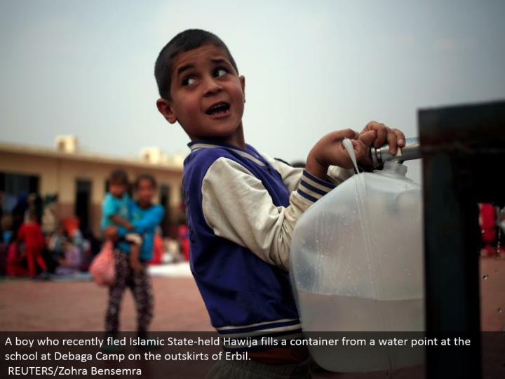 A kid who as of late fled Islamic State-held Hawija fills a compartment from a water point at the school at Debaga Camp on the edges of Erbil. REUTERS/Zohra Bensemra