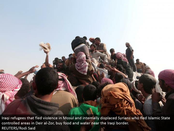 Iraqi outcasts that fled viciousness in Mosul and inside dislodged Syrians who fled Islamic State controlled ranges in Deir al-Zor, purchase sustenance and water close to the Iraqi fringe. REUTERS/Rodi Said