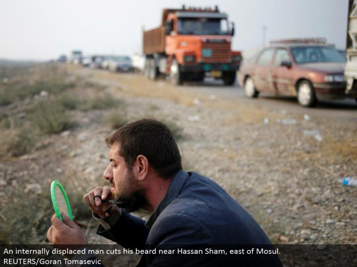 An inside dislodged man cuts his facial hair close Hassan Sham, east of Mosul. REUTERS/Goran Tomasevic