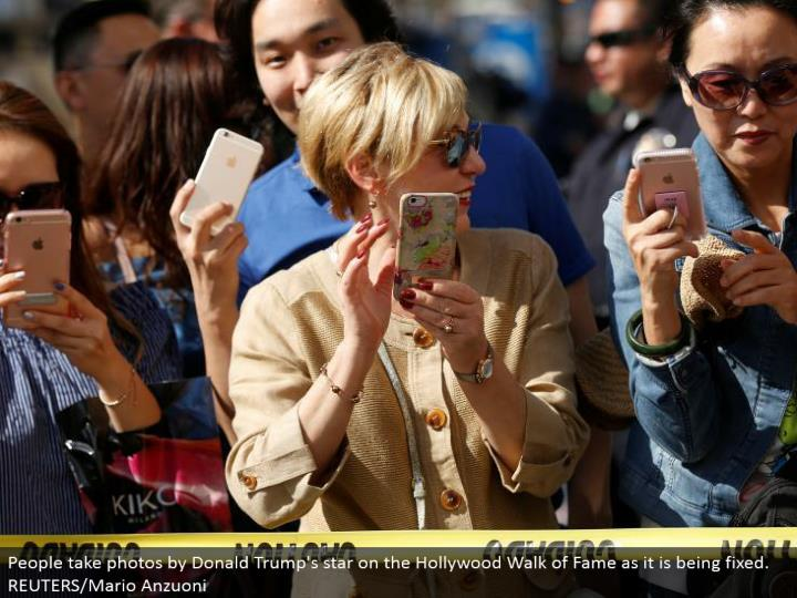 People take photographs by Donald Trump's star on the Hollywood Walk of Fame as it is being altered. REUTERS/Mario Anzuoni