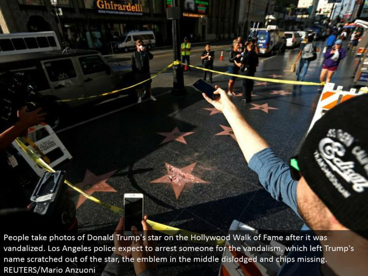 People take photographs of Donald Trump's star on the Hollywood Walk of Fame after it was vandalized. Los Angeles police hope to capture somebody for the vandalism, which let Trump's name scratched alone for the star, the seal in the center unstuck and chips missing. REUTERS/Mario Anzuoni