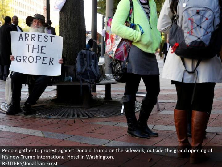 People assemble to challenge Donald Trump on the walkway, outside the great opening of his new Trump International Hotel in Washington.  REUTERS/Jonathan Ernst