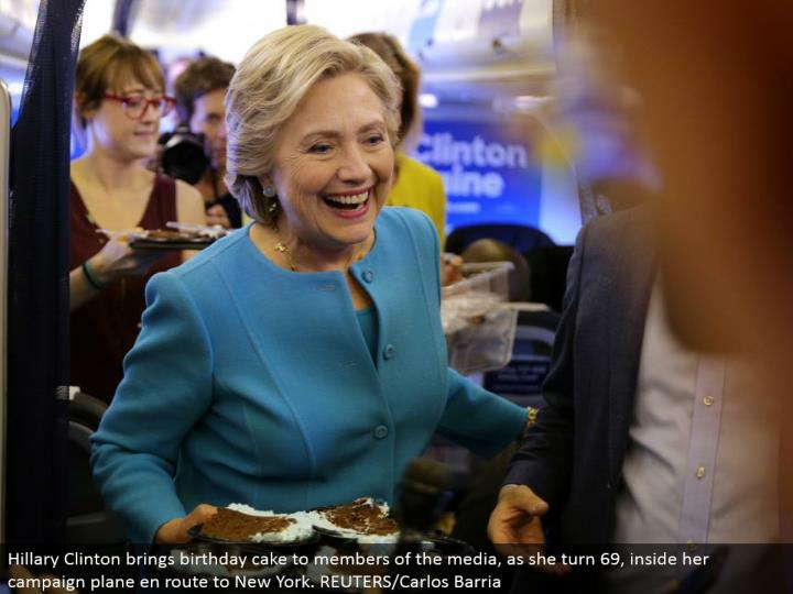 Hillary Clinton conveys birthday cake to individuals from the media, as she turn 69, inside her battle plane in transit to New York. REUTERS/Carlos Barria