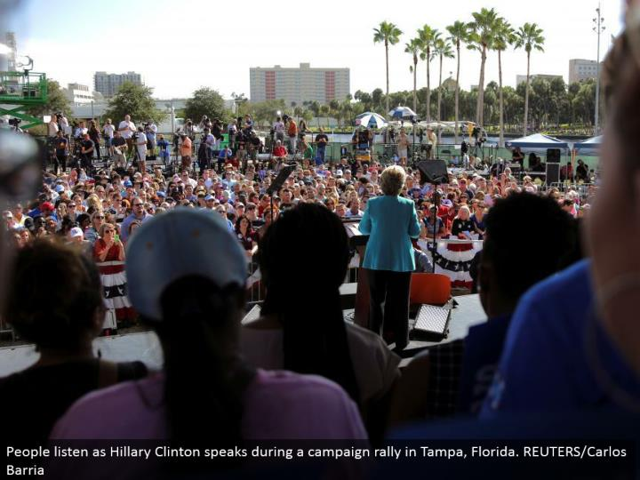 People listen as Hillary Clinton talks amid a battle rally in Tampa, Florida. REUTERS/Carlos Barria