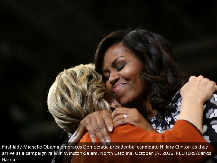 First woman Michelle Obama grasps Democratic presidential applicant Hillary Clinton as they touch ba...