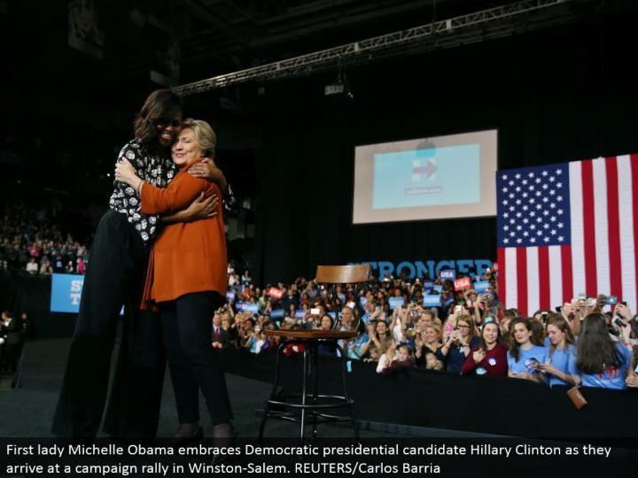 First woman Michelle Obama grasps Democratic presidential applicant Hillary Clinton as they land at a battle rally in Winston-Salem. REUTERS/Carlos Barria